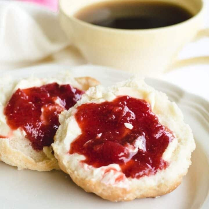 homemade biscuits topped with strawberry rhubarb jam on white plate