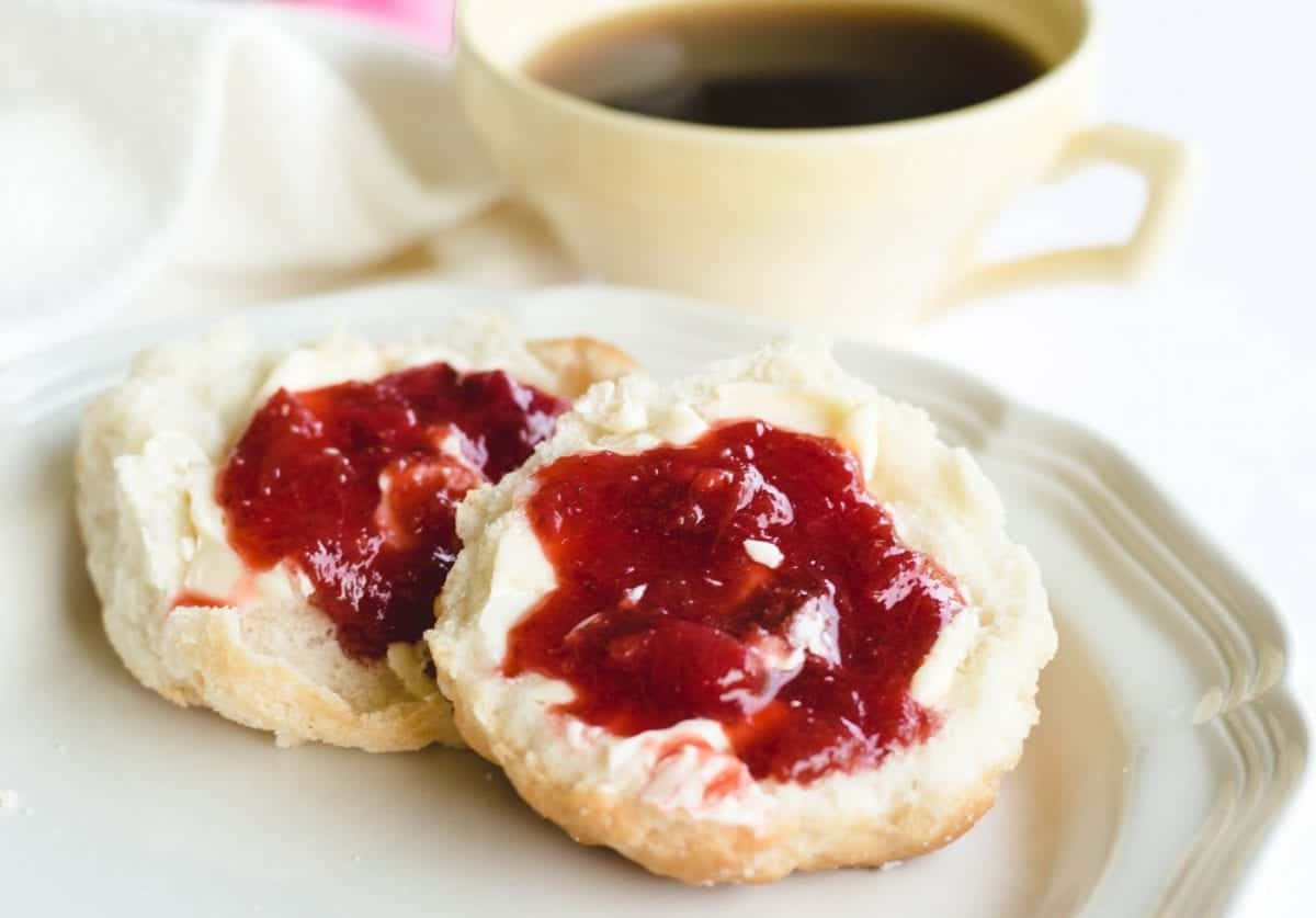 biscuits topped with strawberry rhubarb jam on white plate