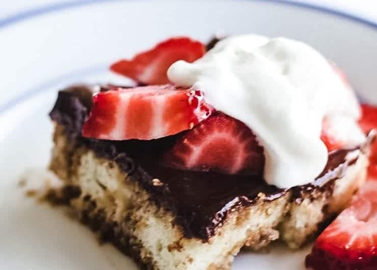 apiece of mochaccino cake topped with strawberries